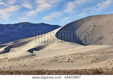 Eureka - a huge sand dune at sunrise. A thin ridge of dunes and deep shadows in the hollows. California, USA