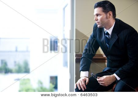 Serious businessman looking out office window