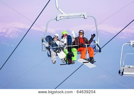 Three smiling snowboarders sitting on ropeway