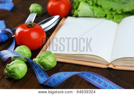 Cutlery tied with measuring tape and book with vegetables on wooden background
