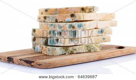 Mouldy bread on cutting board, isolated on white