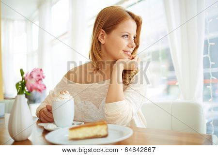Image of serene girl sitting in cafe and looking through window