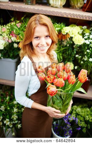 Pretty female florist with big vase of red tulips looking at camera