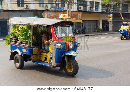 BANGKOK, THAILAND - MARCH 23: Unidentified man drives tuk tuk on March 23, 2014 in Bangkok, Thailand. Tuk tuk is inexpensive and popular form of transport in Bangkok