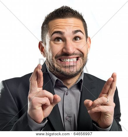 Young Businessman With His Fingers Crossing Over White Background