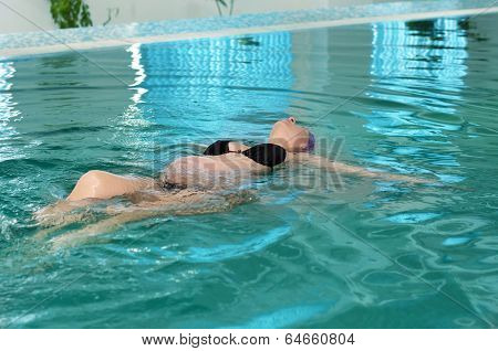 Beautiful young pregnant woman in a swimming pool
