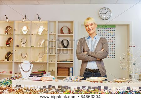 Smiling woman as salesperson behind counter in a jewelry store