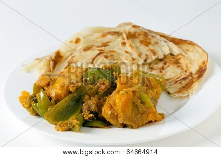 Aloo capsicum, potato and bell pepper vegetarian curry, served with paratha fried flatbread in the traditional way, side view