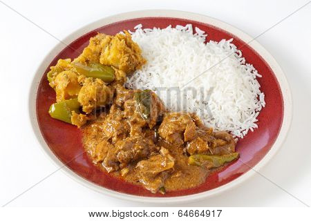 Chettinadu traditional Indian chicken bone-in curry, served with white rice and an aloo capsicum potato and bell pepper vegetable dish.