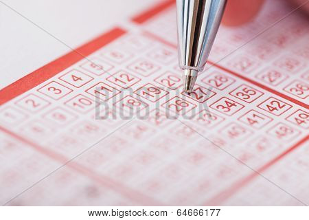 Person Holding Pen Over Lottery Ticket