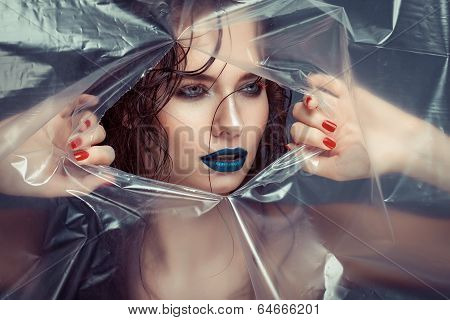 Woman With Creative Eye Makeup Peering Cellophane
