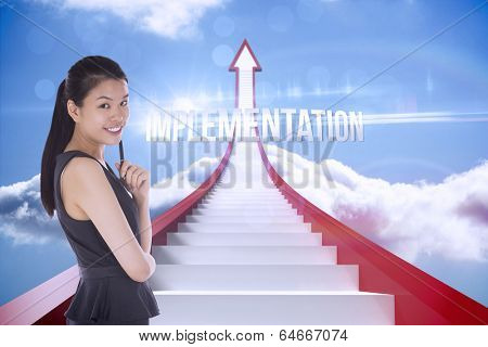 The word implementation and thoughtful businesswoman against red steps arrow pointing up against sky