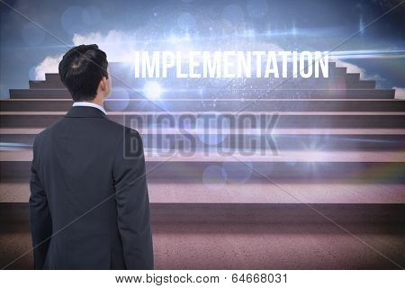 The word implementation and asian businessman against steps against blue sky