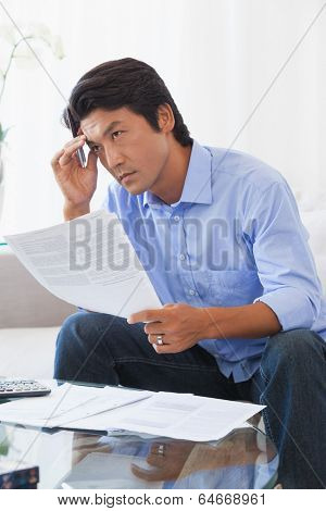Serious man sitting on couch paying his bills at home in the living room