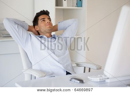 Casual businessman relaxing at desk leaning back in his office