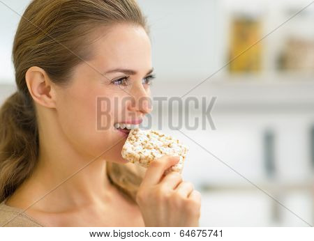 Portrait Of Young Woman Eating Crisp Bread In Kitchen