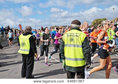 HASTINGS, ENGLAND - MARCH 23, 2014: Marshals watch runners taking part in the annual Hastings Half Marathon race. It is the 30th year the event has been held.