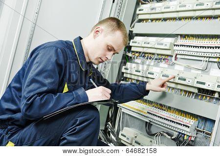 electrician engineer worker inspector  in front of fuseboard equipment in room