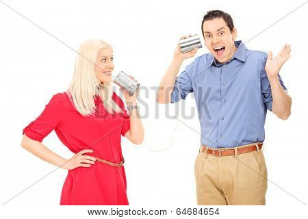 Young couple having fun with a tin can phone isolated on white background