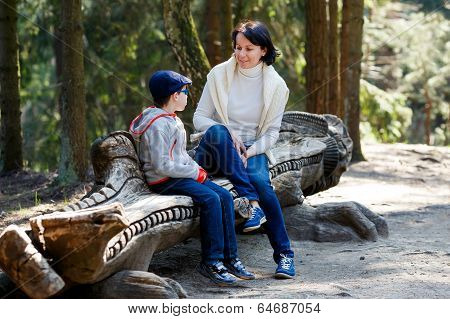 Mother and her little son sitting on a bench