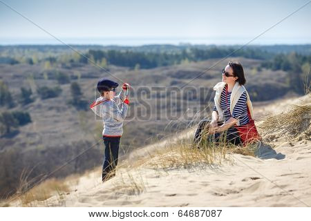 Little boy photographing his mother outdoors