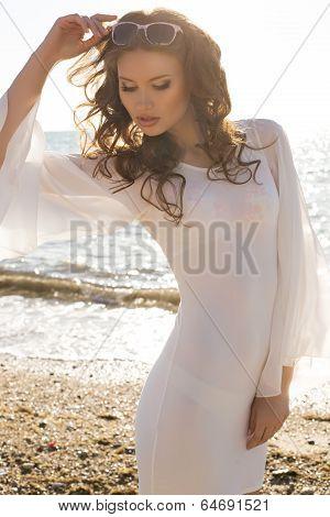 beautiful girl with dark hair in white dress posing on beach
