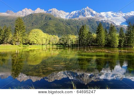 Gorgeous reflection in the smooth water of the lake in the park.  Snowy mountains and evergreen forests in the famous mountain resort of Chamonix