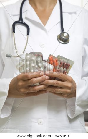 Doctor Holding Out A Handful Of Pills