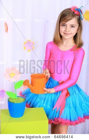 Beautiful small girl in petty skirt watering flowers on decorative background