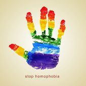stock photo of homosexuality  - text stop homophobia and a handprint with the colors of the rainbow flag on a beige background - JPG