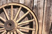 stock photo of wagon  - Wooden wagon wheel leaning against weathered barn - JPG