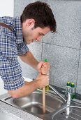 picture of plunger  - Young Handsome Man Using Plunger In Kitchen Sink