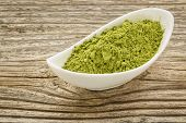 image of moringa  - moringa leaf powder in a small ceramic bowl against grained wood - JPG