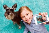 stock photo of schnauzer  - little girl taking photo of herself and her dog with mobile phone camera - JPG