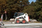 stock photo of bobcat  - A small excavator Bobcat parked at construction site - JPG