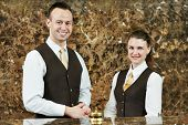 picture of receptionist  - Receptionist or concierge workers standing at hotel counter - JPG