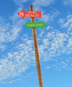 image of nudist beach  - wooden arrow direction signs post to the nude and family beaches against a blue sky - JPG