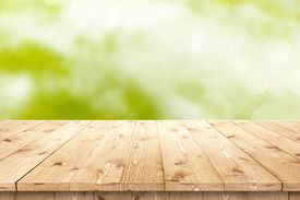 stock photo of joinery  - Empty wooden table in a sun drenched summer garden for product placement or montage with focus to the table top in the foreground - JPG