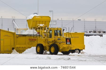 JFK Airport January 2011 Wheel loader machine unloading snow to snow melter with airport work crews after large storm at JFK Airport on January 13, 2011 clearing off taxi ways and run ways.