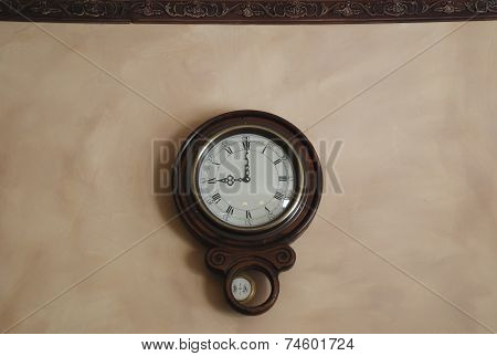 Antique pendulum wall clock showing the time