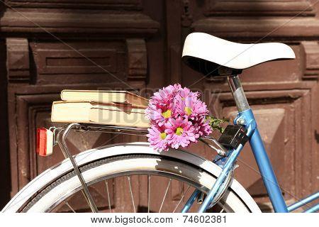 Old bicycle with flowers in metal basket on brown door background