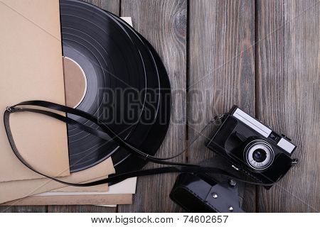 Vinyl records and paper covers and camera on wooden background