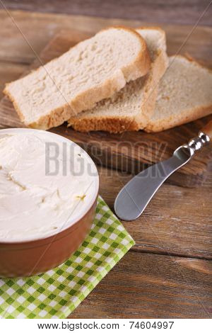 Fresh homemade butter in bowl and sliced bread, on wooden background