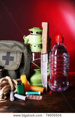 Emergency preparation equipment on wooden table, on dark color background