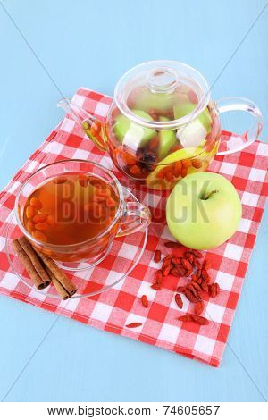 Goji berries drink in glass cup, ripe apple and cinnamon, fruit drink in glass teapot on red checkered napkin on light blue wooden background