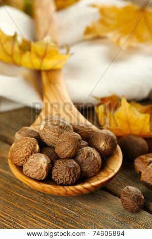 Nutmeg in wooden spoon on table close up