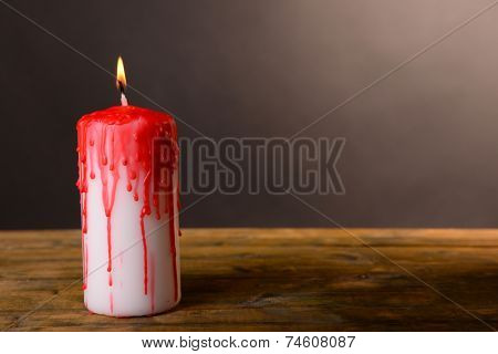 Bloody candle for Halloween holiday, on wooden table, on dark background
