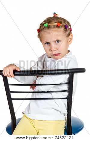 Offended little girl on a chair