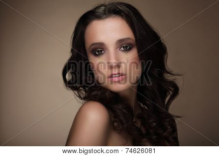 Image Of Young Brunette With Golden Tears On Her Face