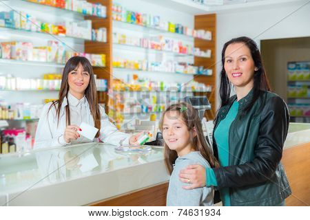 Cheerful pharmacist chemist woman giving vitamins to child girl in pharmacy drugstore, selective foc